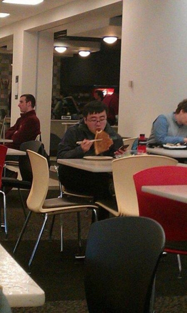 This kid eating pizza with chopsticks.
