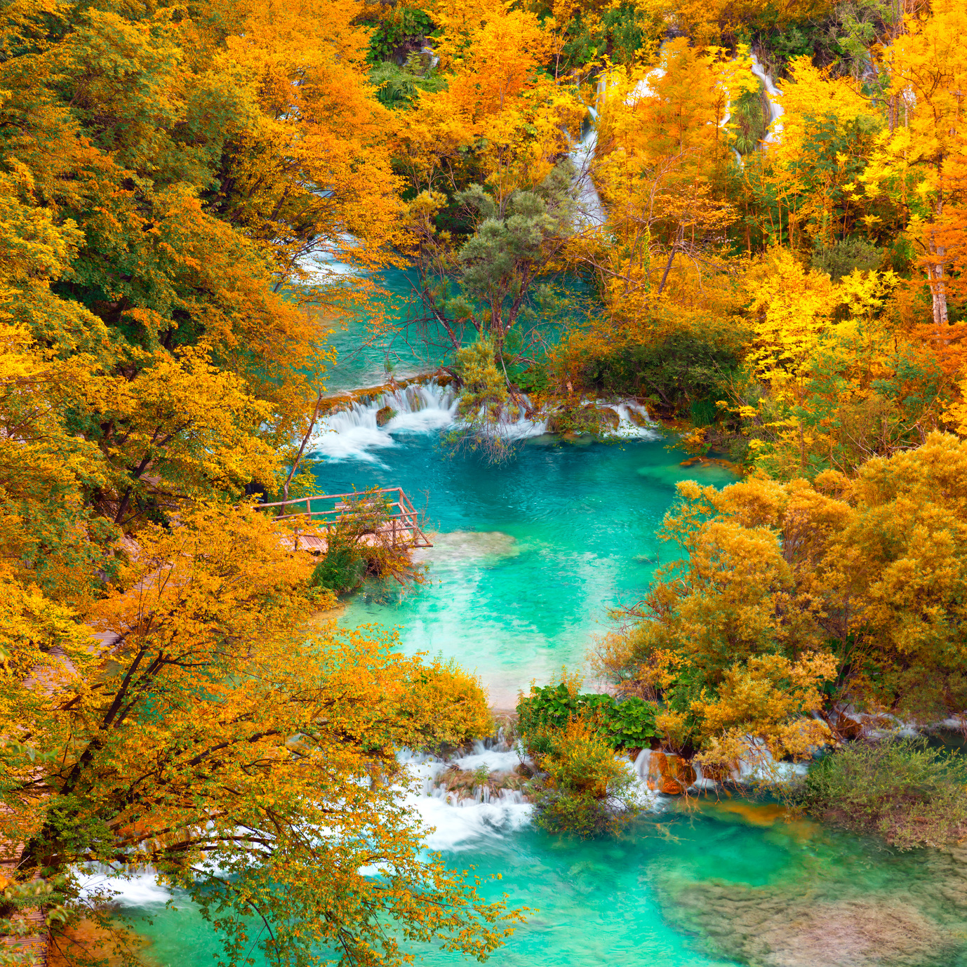 Aerial Autumn view on waterfalls and lakes with turquoise water and golden trees in the Plitvice Lakes National Park, Croatia, Europe