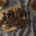 Dark chocolate on trencher and coffee beans